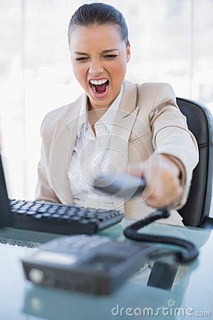 Angry-businesswoman-screaming-hanging-up-phone-bright-office-33409232
