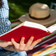 Person-reading-red-covered-book-near-grass